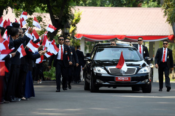 A car, carrying Indonesian President Joko Widodo and first lady Iriana Widodo, is pictured before the inauguration of IndonesiaÕs President Joko Widodo for the second term at the Merdeka Palace in Jakarta