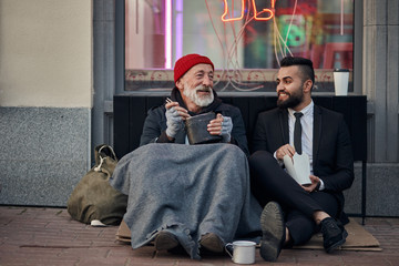 Handsome businessman in suit sitting on floor with homeless man together, listen to his story of life. Contrast people, rich and poor, but doesn't matter Fotomurales