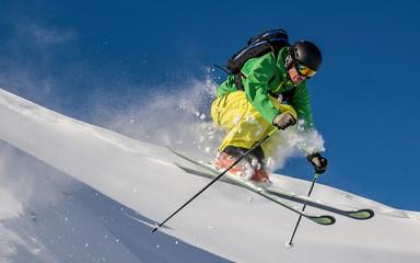 Freestyle Skier jumping off a rock in the Austrian Alps, Arlberg, Salzburg, Austria