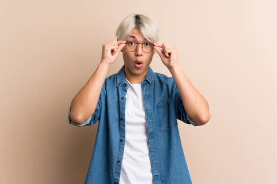 Young asian man over isolated background with glasses