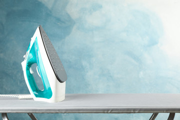 Fototapeta Iron on ironing board against blue background, space for text obraz