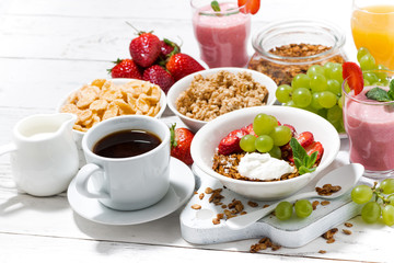delicious and healthy breakfast with fruits, granola and milkshake on white background