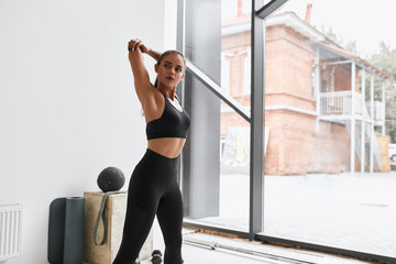 Attractive female warms up arms at gym. Dressed in black leggins and topic. Window background