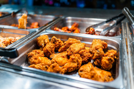 Fried chicken thighs buffet bar self serve with tongs in grocery store, restaurant or catering event with crisp skin and unhealthy food