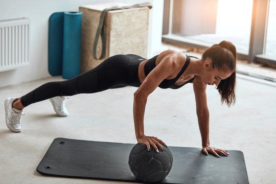 Side view on fit woman in sportswear push up in fitness studio, window background.