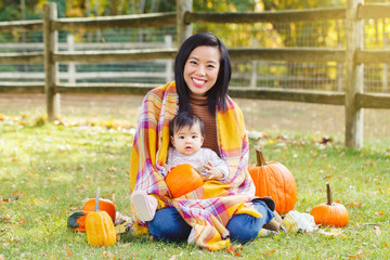 Portrait of cute adorable funny Asian Chinese mother with baby girl sitting in autumn fall park outdoor with yellow orange pumpkins. Halloween or Thanksgiving seasonal concept.