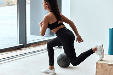 Side view on strong caucasian female leaning leg widely on box, working out in gym. Fit box for stretching legs
