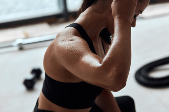 Fit woman with strong muscles after active training in fitness gym. closeup Sweat skin. Kettlebells behind