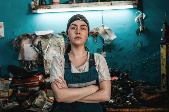 The concept of small business, feminism and women's equality. A young woman in working clothes posing in front of a car workshop. Close up