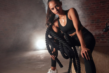 Young sporty female sit in gym holding battle rope. Crossfit, sport, healthy lifestyle concept Fototapete