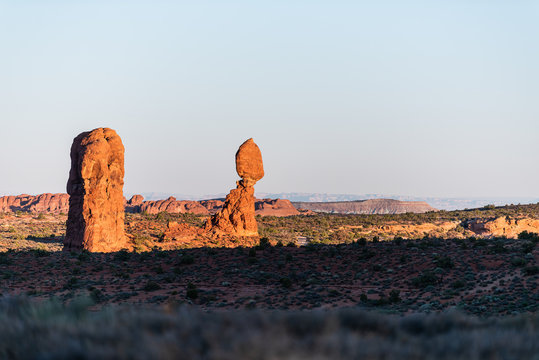 Famous balanced rock in Arches National Park butte with horizon in Utah during morning sunrise with orange sunlight color