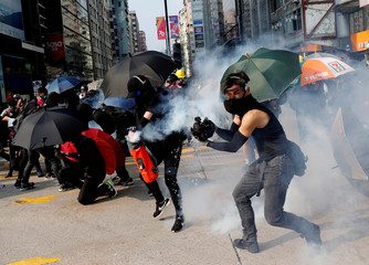 An anti-government demonstrator puts out a tear gas canister with a bag holding water during a protest in front of  Tsim Sha Tsui Police Station in Hong Kong