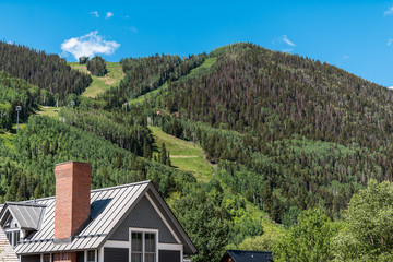 Ski resort town house with modern roof architecture typical building exterior in Telluride, Colorado with green mountain slope in summer