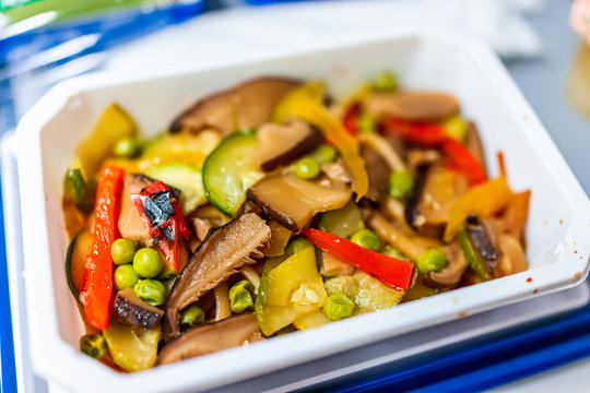 Healthy vegan asian stir fry food vgml hot meal on airplane flight tray with mushrooms, teriyaki noodles and vegetables closeup