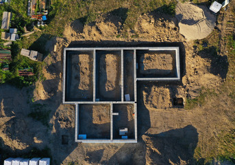 Aerial drone top down view on construction site with reinforced concrete house foundation, brick wall and materials like wall blocks and sand Wall mural