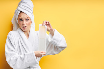 A face of young beautiful woman full of fear, wearing bathrobe and towel use wax strips for epilation after bathing. isolated over yellow background