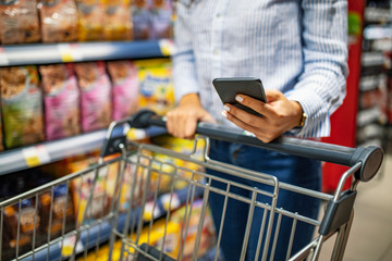 Shopping list. Woman with smartphone in store. grocery shopping. gadgets and shopping.  Picture of young cheerful woman in supermarket with shopping trolley choosing products and using phone.