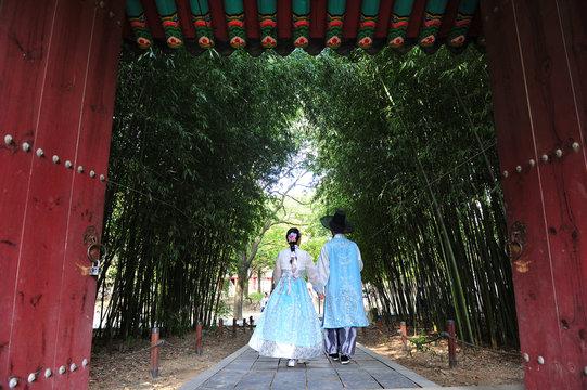 Korean couple dressed in hanbok and touring the  Gyeonggijeon at Korean traditional house Village in Jeonju, Jeollabuk-do, South Korea.