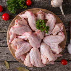 Viande Raw chicken wings on a wooden cutting board. Top view