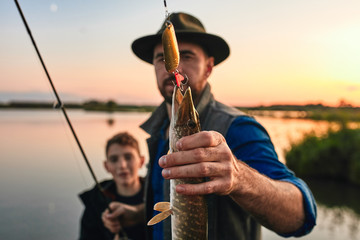 Positive man with teenager boy standing together and showing catch fish outdoors