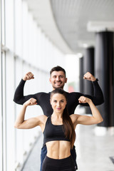 Athletic man and woman after fitness exercise show biceps standing at gym