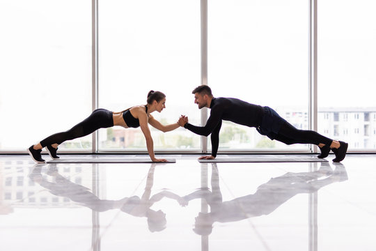 Young sporty couple working out together in a gym doing plank exercises while holding each other for one hand.