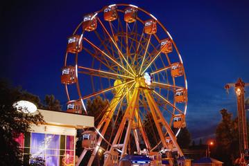 Foto op Aluminium Amusementspark Illuminated ferris wheel in amusement park at a night city