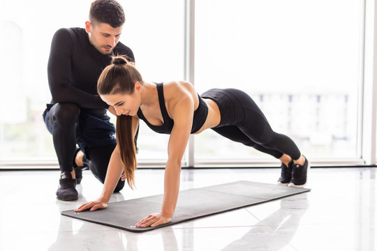 Sporty young couple doing plank exercise in gym. Young man trainer work with fitness woman at gym