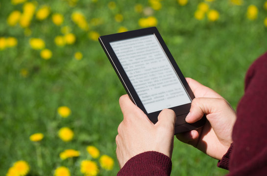 A man is reading an electronic book at spring sunny day. Blurred text. Only his hands are on the picture. Dandelion field at background.