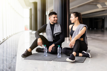 Young healthy couple relaxing after workout in the gym Fototapete