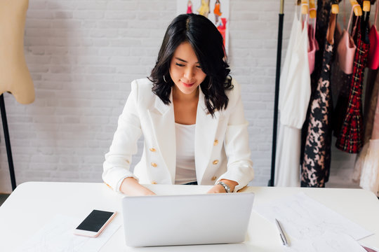 Contemporary confident Asian lady entrepreneur in stylish jacket working on laptop with garment hanger on background