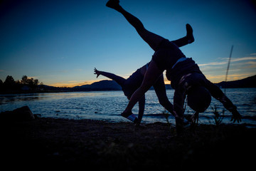 next to lake silhouette of a group of people doing a cartwheel during sunset