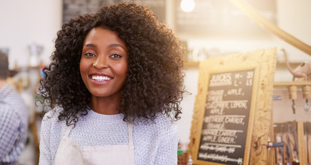 Smiling African American entrepreneur barista standing in a bright cafe