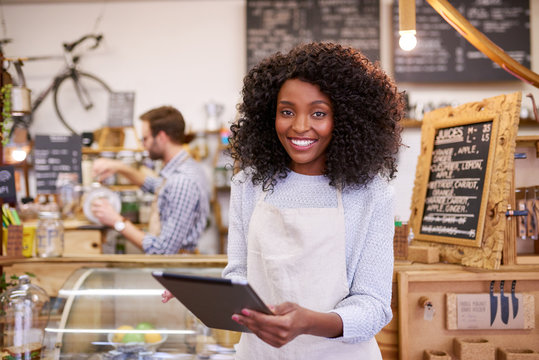 Smiling African America barista using a tablet in her cafe