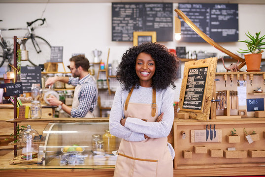 Smiling young African American female barista standing in her cafe