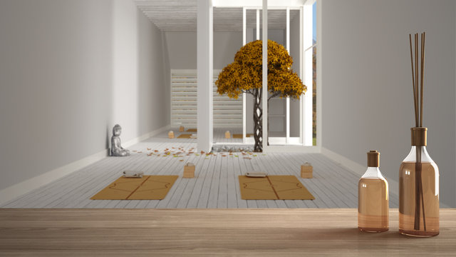 Wooden table top or shelf with aromatic sticks bottles over empty yoga studio, open space with mats and accessories, zen garden, autumn tree, falling leaves, ready for yoga practice