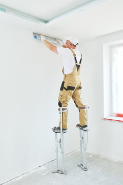 Painter in stilts with putty knife. Plasterer smoothing ceiling surface at home renewal