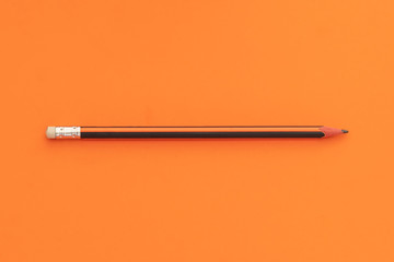 Wooden Pencil on Orange Background Dividing Space Into Halves