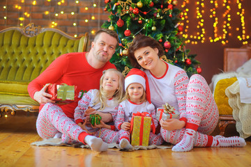 Portrait of a happy family in pajamas, sitting in pajamas near the Christmas tree with puffs in their hands and having fun