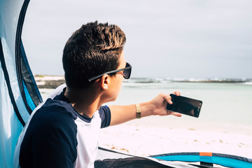 Young caucasian people handsome boy viewed from back taking picture with modern technology device phone - travel and camping concept - beach tropical background