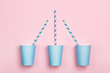 Pink paper drinking cup and striped straws on duotone pink and blue background. Birthday party celebration abstract fashion baby shower concept. Minimalist pastel style.