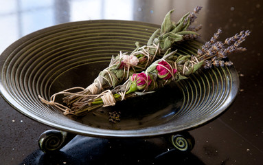 Sage, rose and lavender smudge sticks in burning bowl