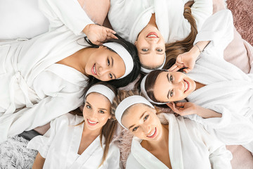Happy young women lying on bed during hen party, top view