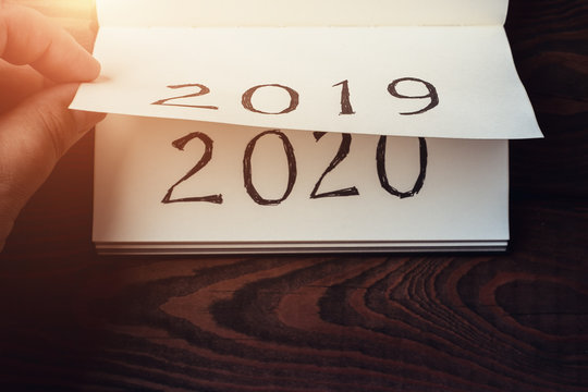 New Year 2020 coming concept. Male fingers flips notepad or calendar sheet. 2019 is turning, 2020 is opening, top view