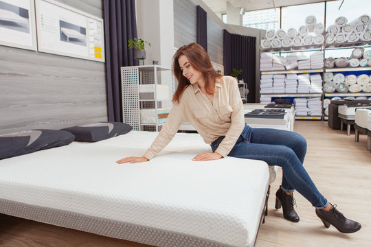 Attractive female customer sitting on a new bed at furniture store, choosing orthopedic mattress to buy