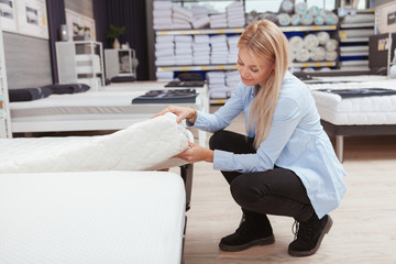 Young woman shopping for new orthopedic bed at furniture store, copy space. Female customer examining mattress for sale