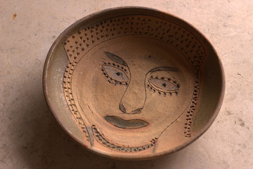Clay bowl with primitive face design