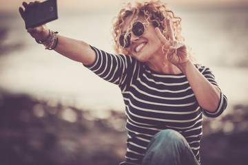 Cheerful happy beautiful curly trendy woman taking selfie picture with modern phone - people enjoying the outdoor technology leisure activity -   defocused beautiful background