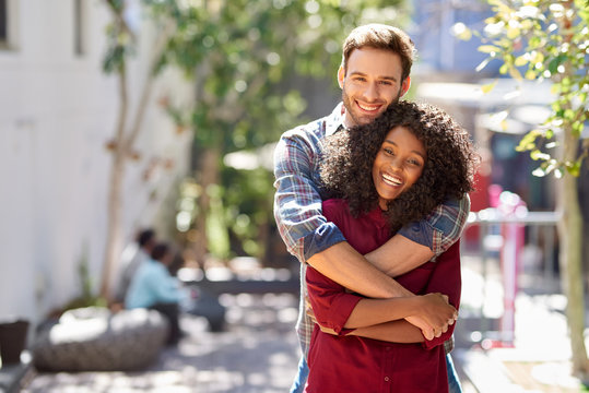 Diverse young couple hugging while standing together on a sidewalk