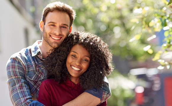 Diverse couple affectionately standing together ouside on a sunny day